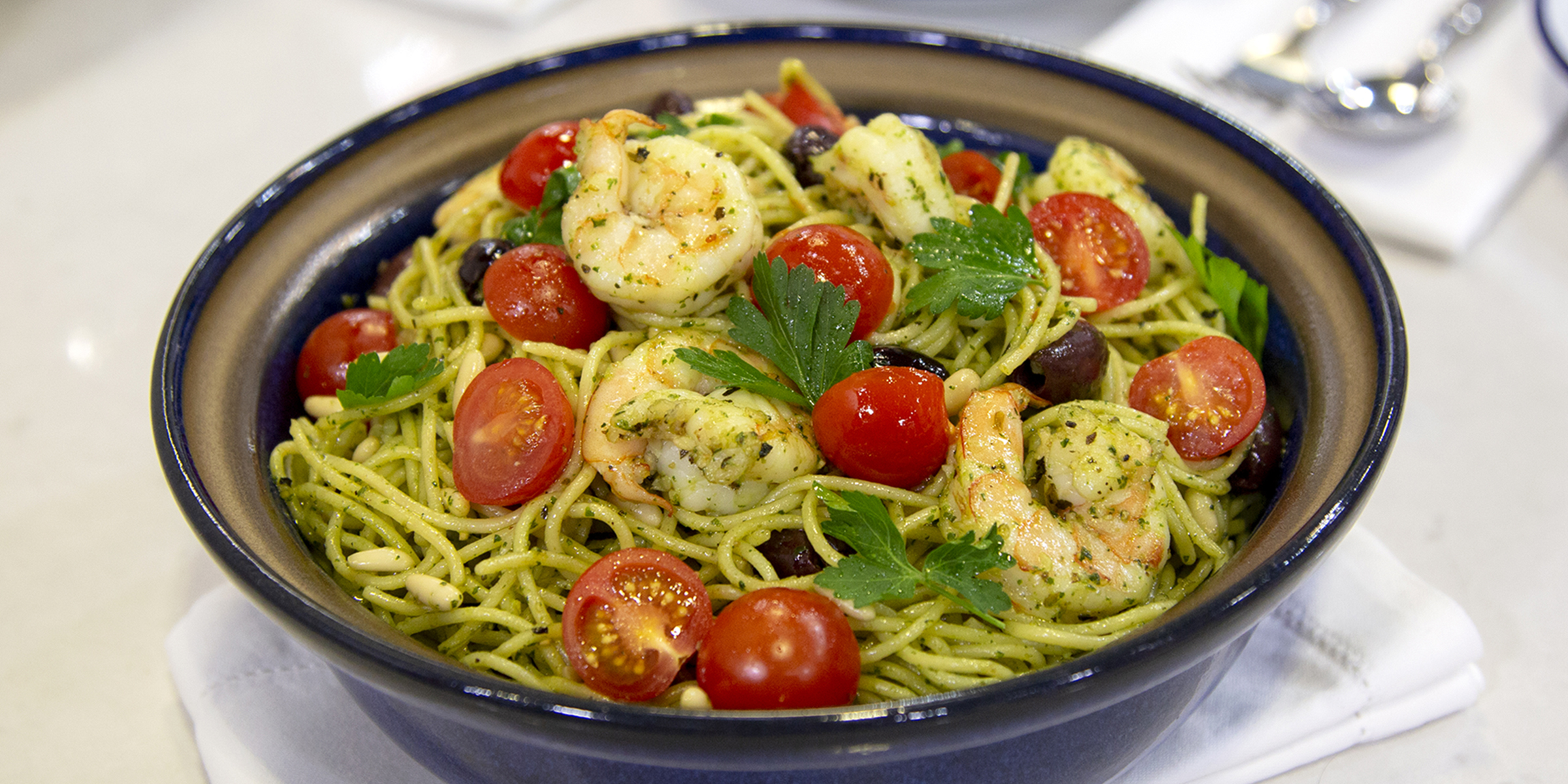 Add Mediterranean flair to pasta with shrimp, olives and pesto sauce