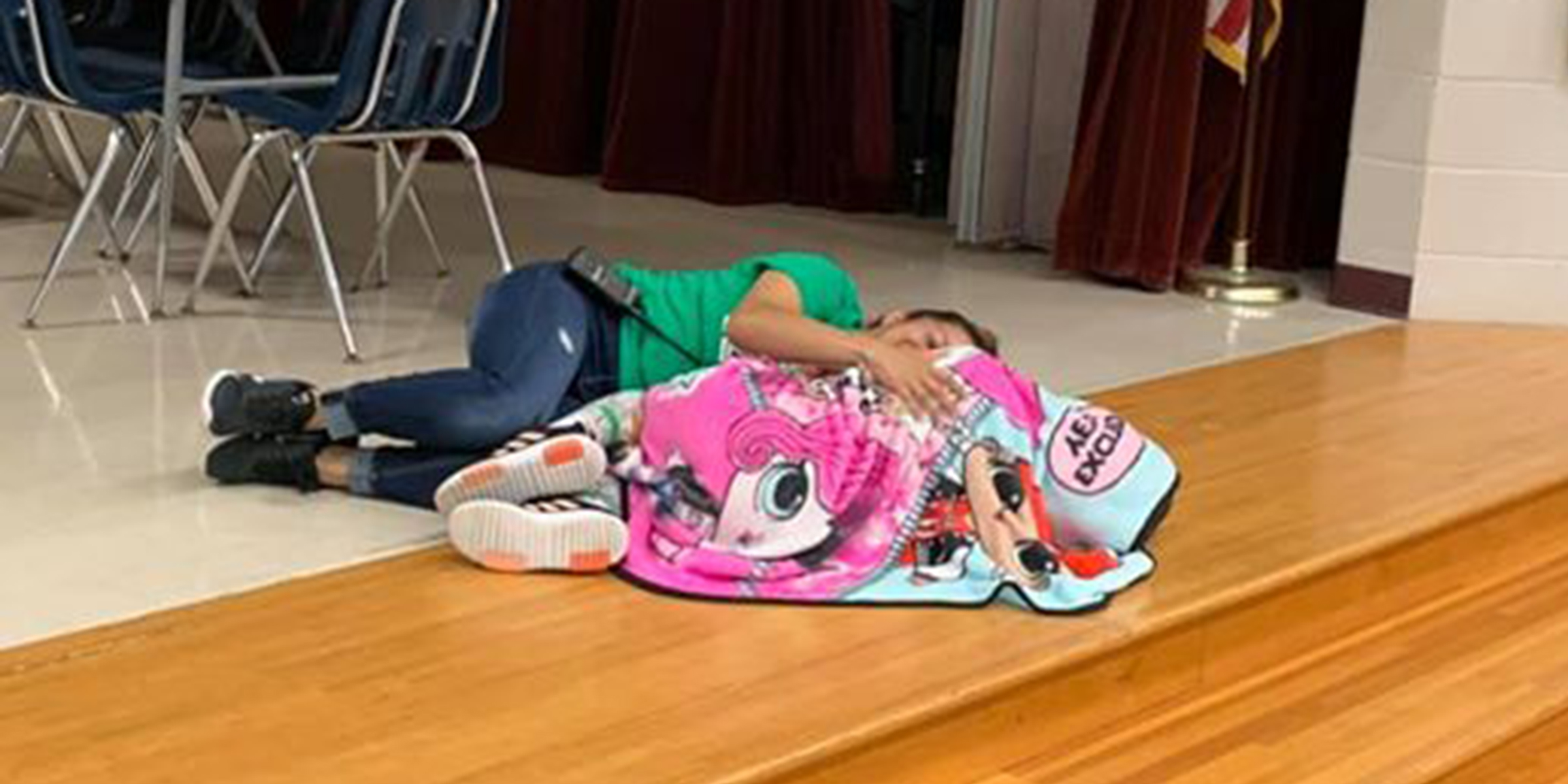 School janitor lays on the ground to comfort girl who has autism