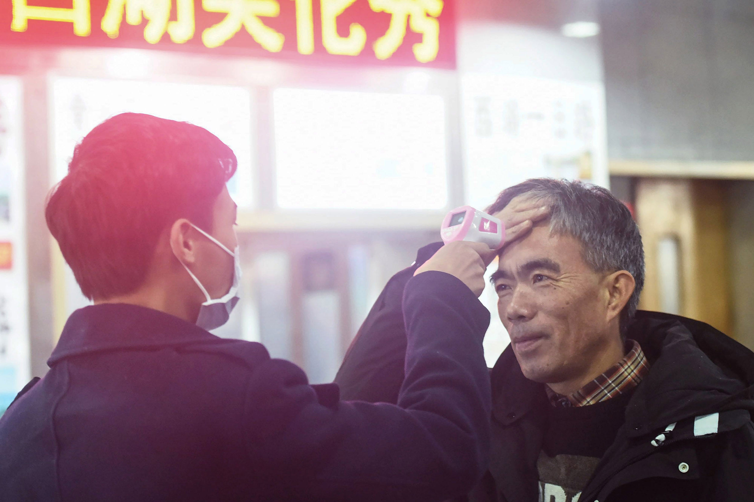 Image: A staff member checks the body temperature of a passenger after a train from Wuhan arrived at Hangzhou Railway Station in Hangzhou, China's eastern Zhejiang province