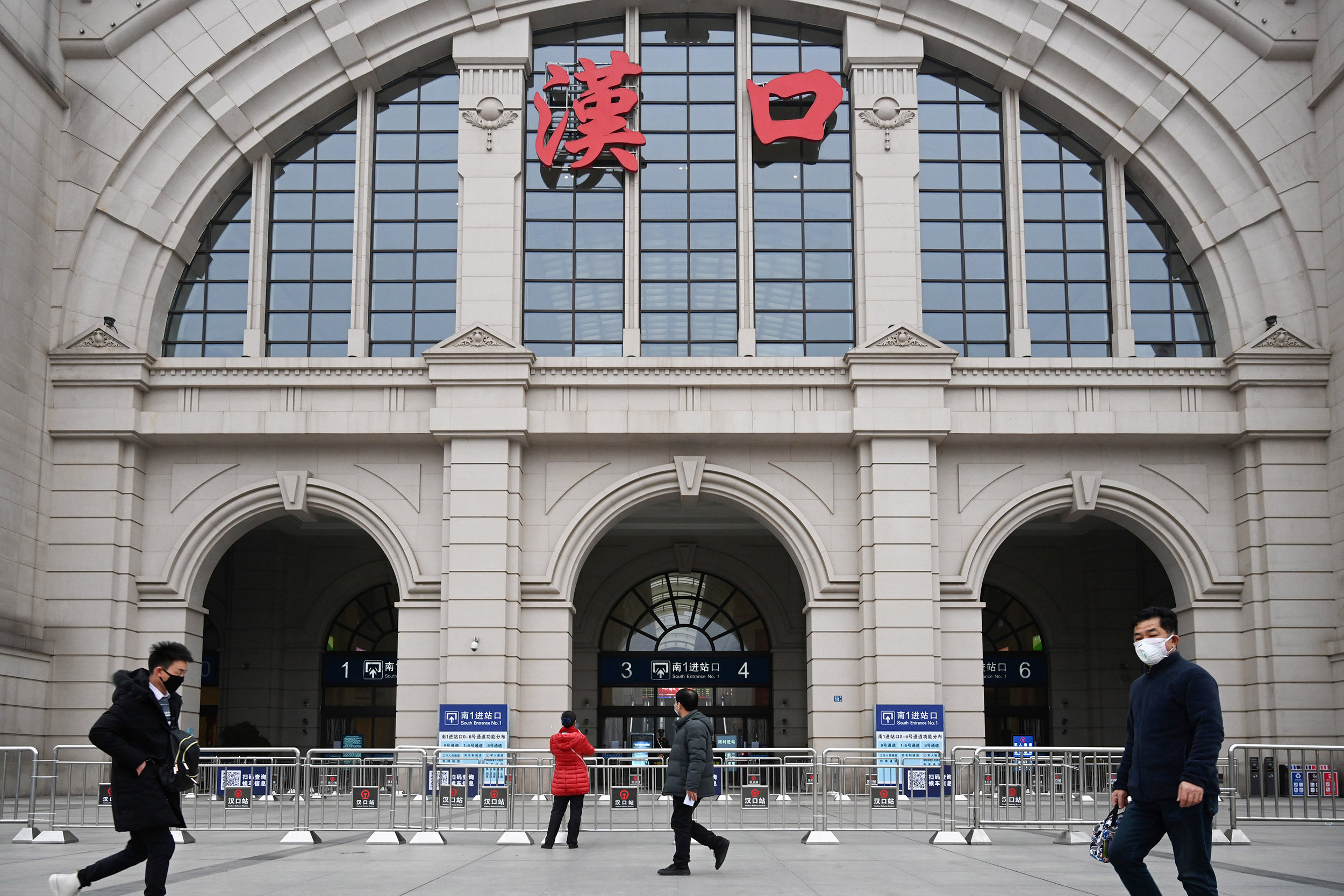 Image: People walk past the closed Hankou Railway Station after the city was locked down following the outbreak of a new coronavirus in Wuhan
