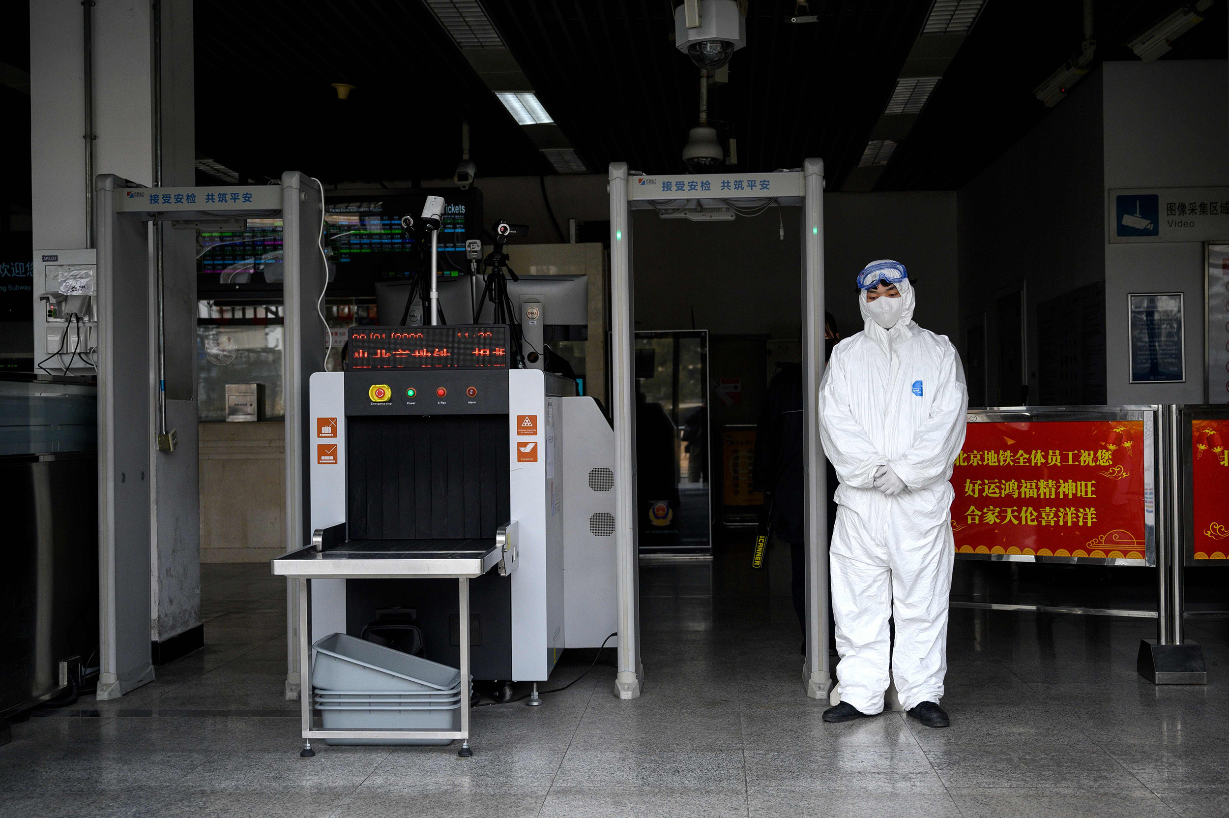 Image: Security personnel wearing protective clothing to help stop the spread of a deadly SARS-like virus at the entrance of subway station in Beijing