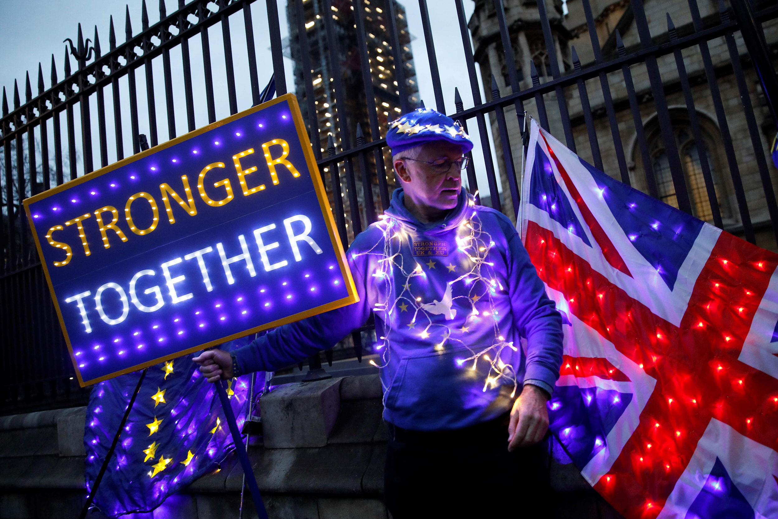 Image: Anti-Brexit protester holds illuminated Union and E.U. flags near the Houses of Parliament in London