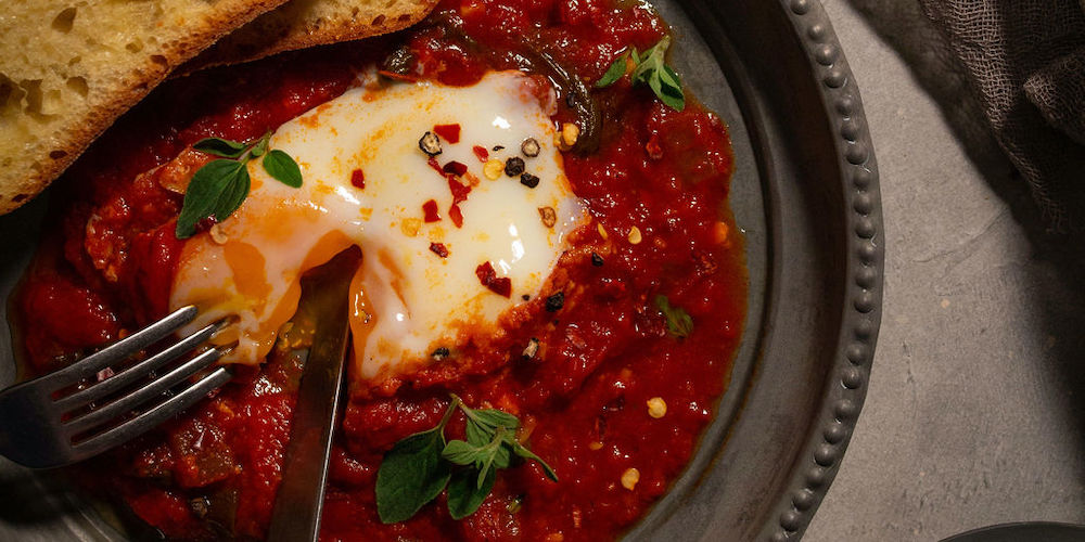 Bake eggs in a spicy tomato sauce and serve with garlic bread for dipping