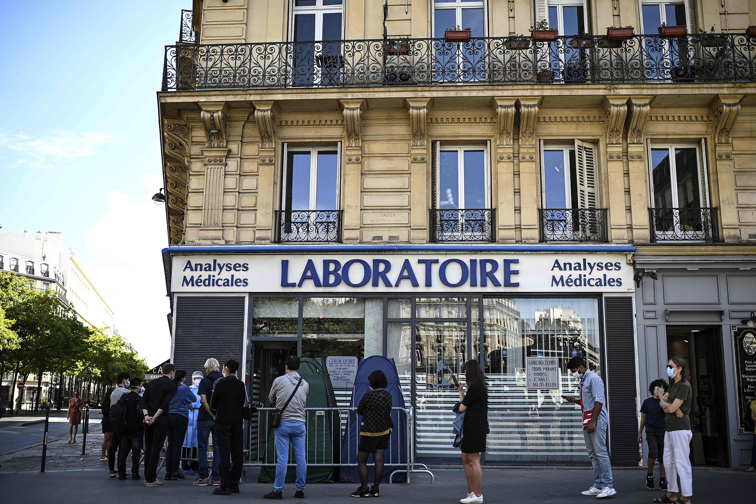 Image: People stand in line as they wait for a COVID-19 test in Paris. (Christophe Archambault / AFP - Getty Images)