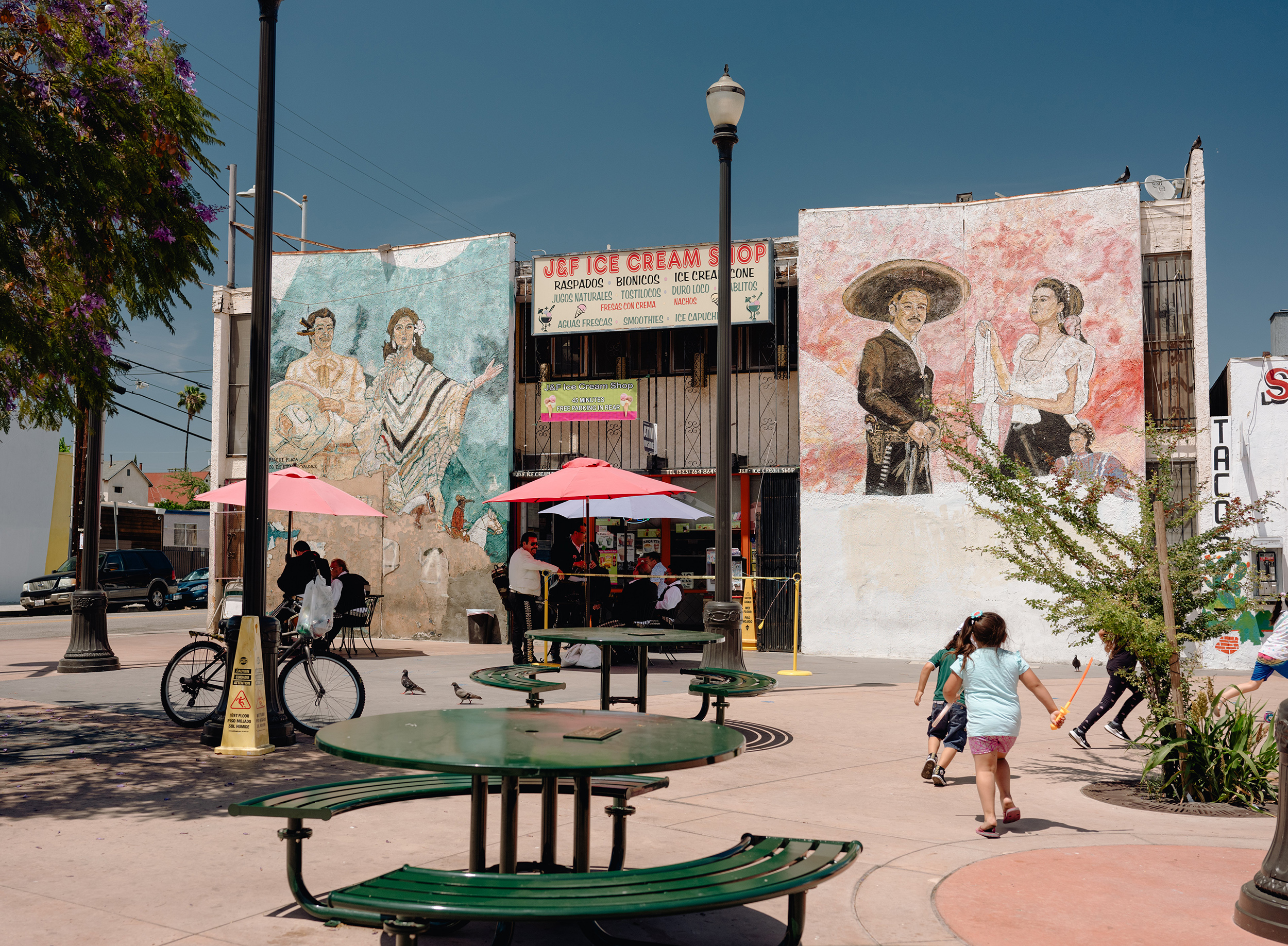 Children play by an ice cream shop surrounded by murals in Boyle Heights.