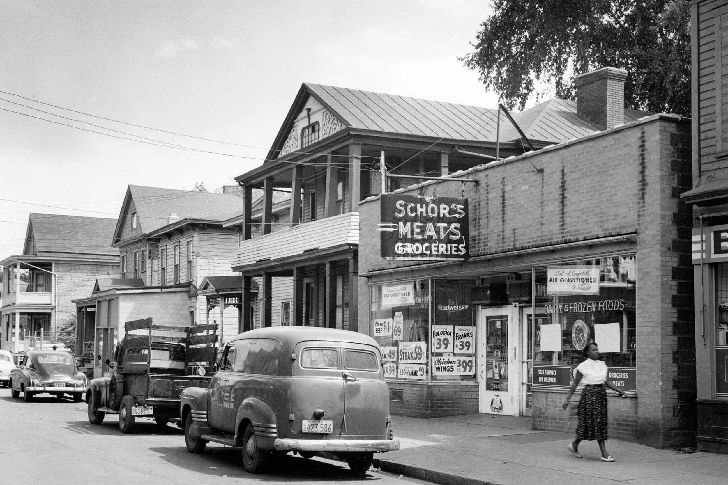 A woman walks past Schor's Meats at 604 Harrison Street in 1963.
