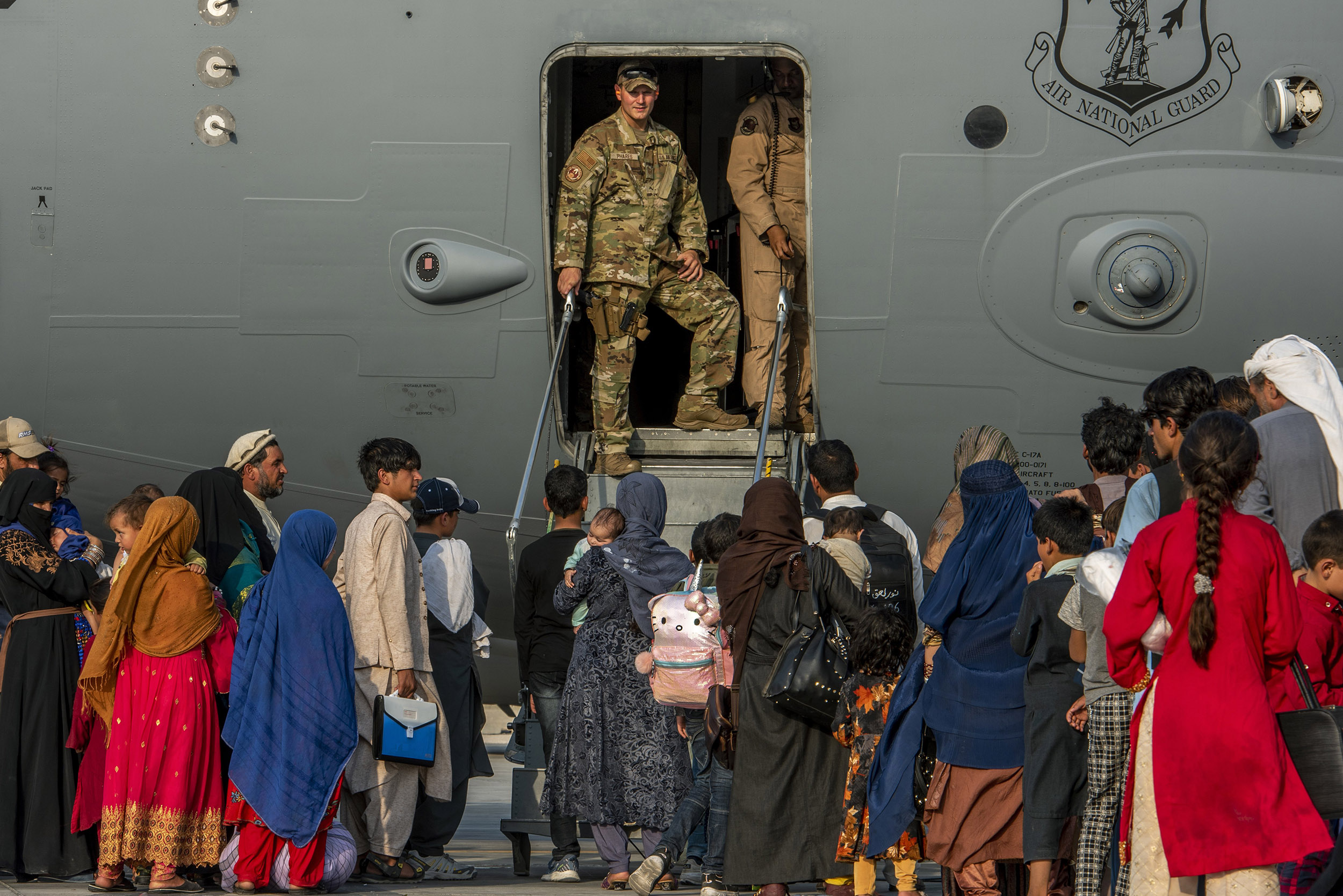As airlift accelerates, evacuees say they are facing dire conditions in transit limbo