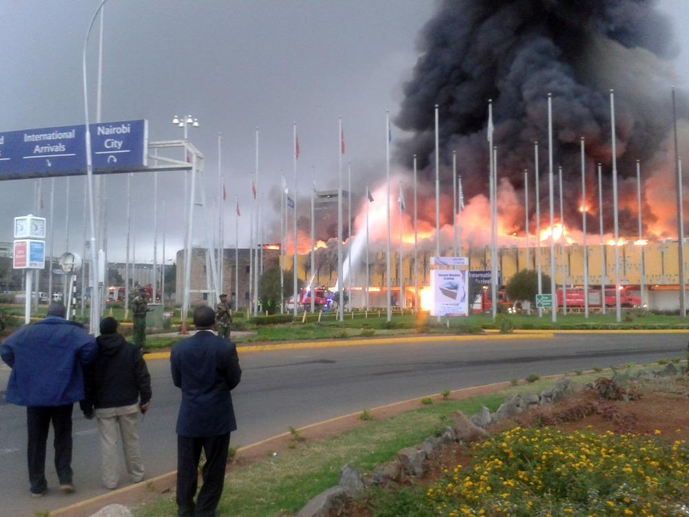 Onlookers watch as black smoke billows from the international arrival unit of Jomo Kenyatta International Airport in Nairobi, Kenya, on Wednesday.