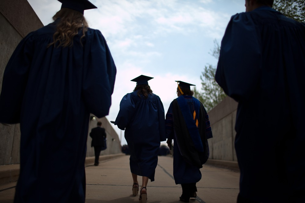 Alumni of the University of Illinois at Urbana-Champaign school of business emerge from a tunnel of the State Farm Center after participating in comme...