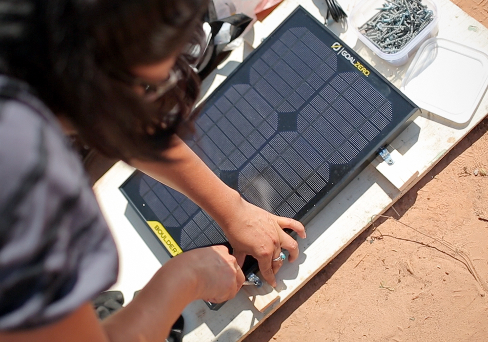 Adrian Manygoats installs a solar panel on a house without electricity in the Navajo reservation.