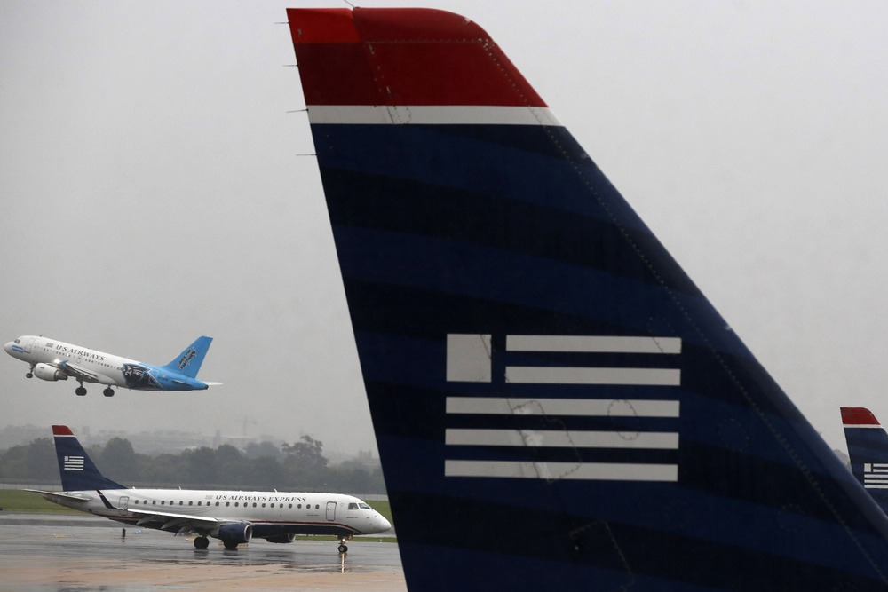 U.S. Airways jets are seen at Reagan National Airport in Washington last month. The Justice Department has challenged a merger between US Air and Amer...