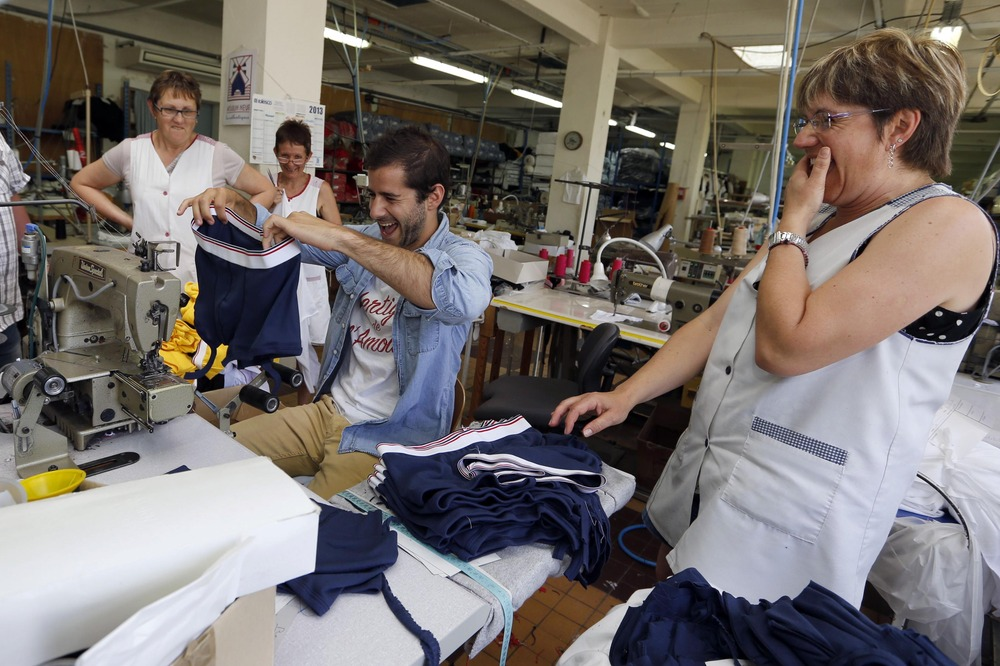 Guillaume Gibault, 27, center, founder and designer of Le Slip Francais men's underwear brand, works on a sample. Gibault offers a