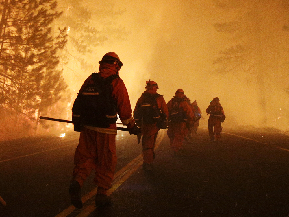 Inmate firefighters walk along state Highway 120 as firefighters continue to battle the Rim Fire near Yosemite National Park, Calif., on Sunday, Aug. ...