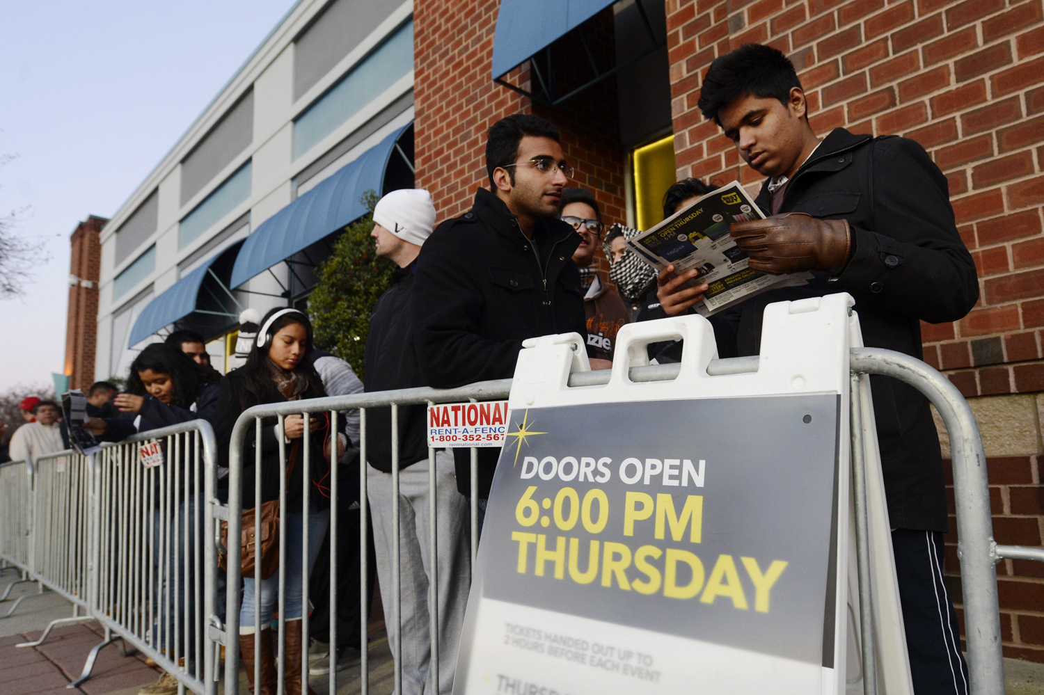Shoppers check out a list of sale items while waiting in a line for a Best Buy to open on Thanksgiving Day in Alexandria, Va.