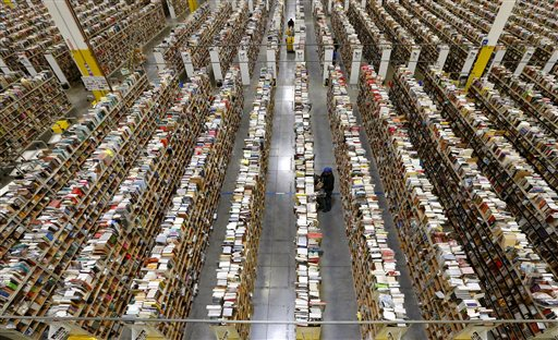 An Amazon.com employee stocks products along one of the many miles of aisles at an Amazon.com Fulfillment Center on