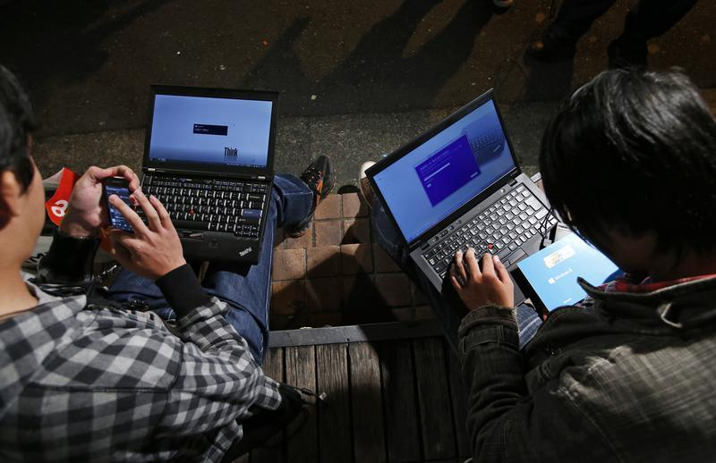 Men install Microsoft Corp's Windows 8 operating system on their laptops, as Windows 8 goes on sale after midnight, along a street at the Akihabara di...