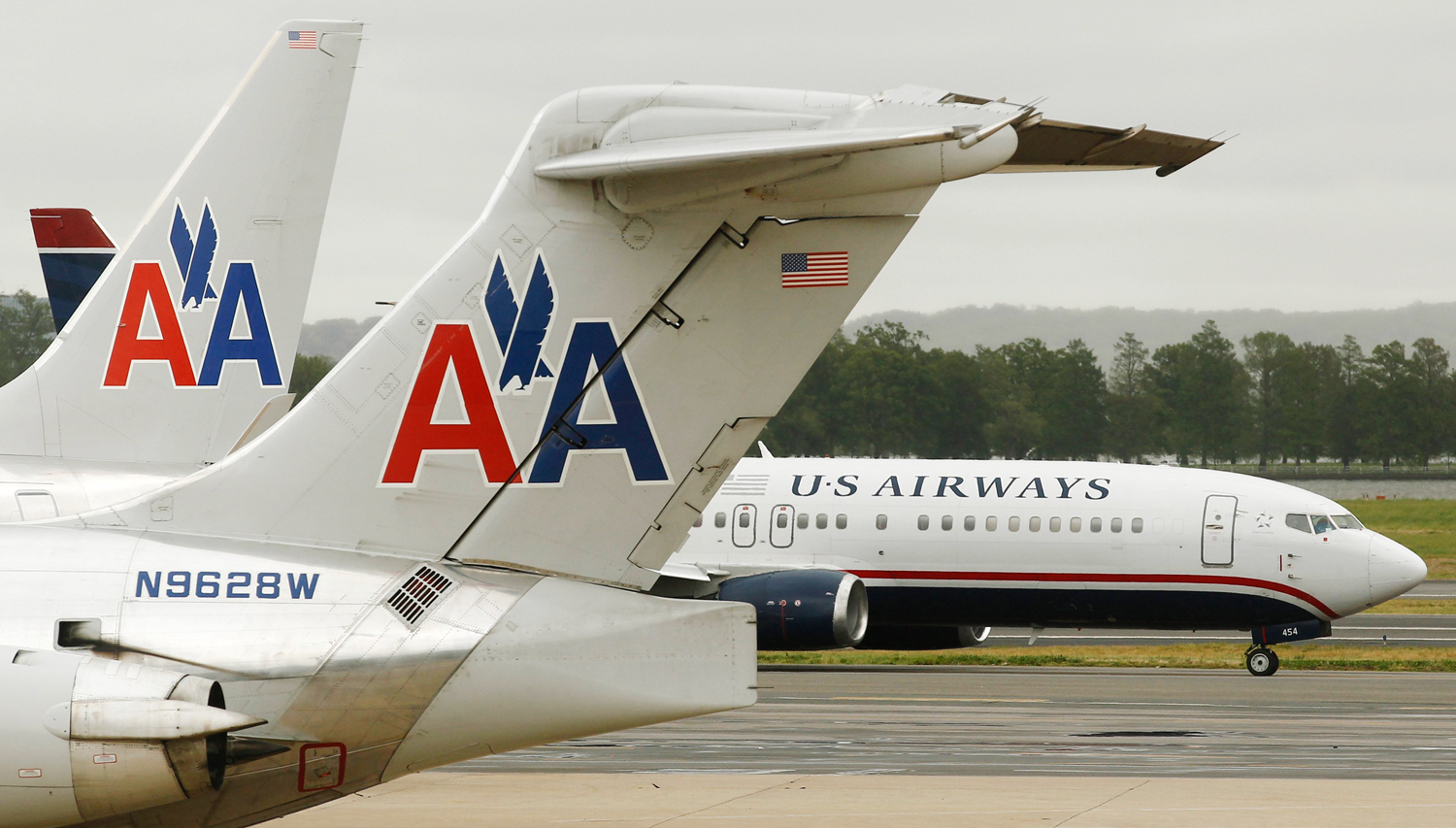 A US Airways plane passes American Airlines planes at Ronald Reagan National Airport in Washington in this April 23, 2012 file photo. AMR Corp and U.S...
