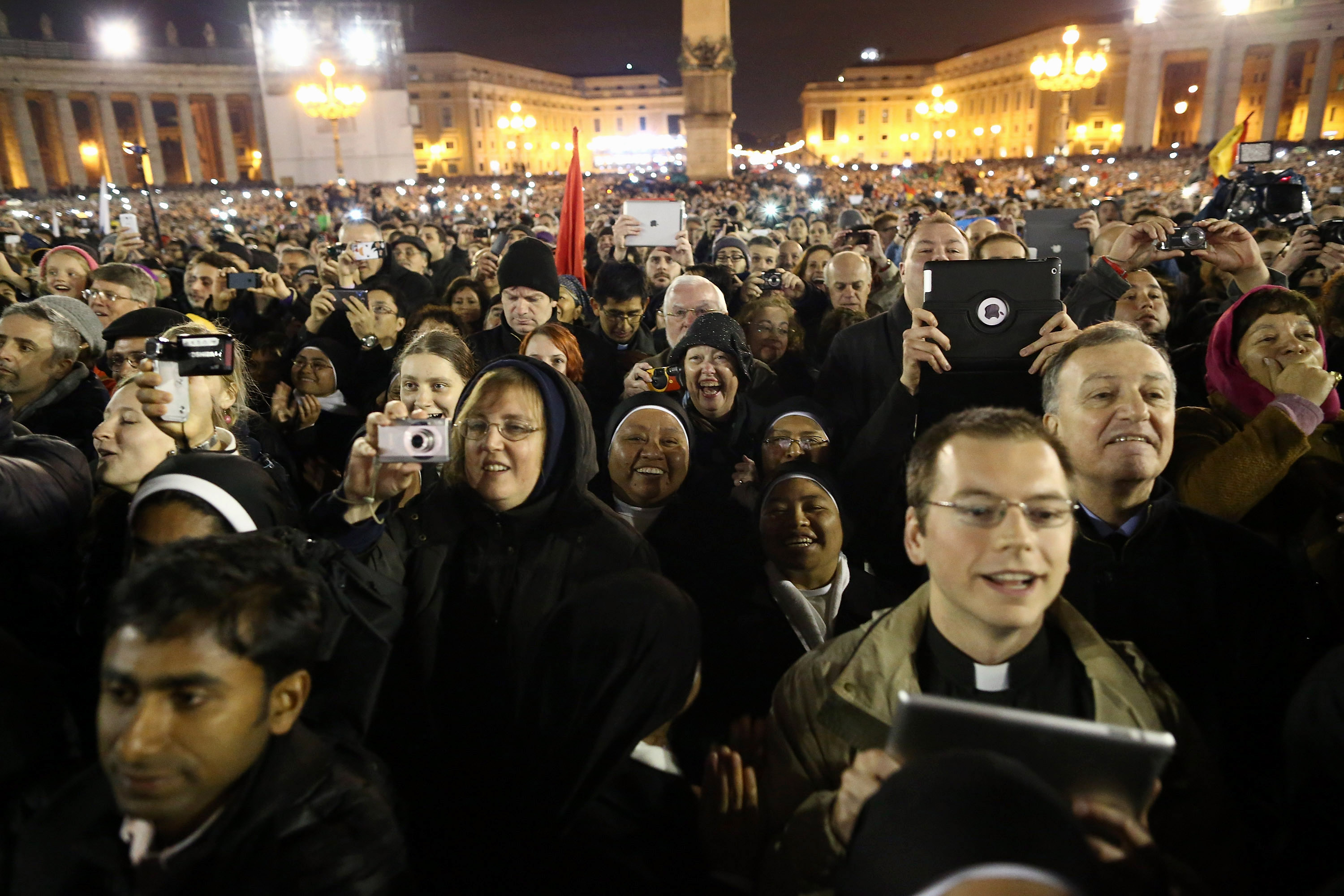 VATICAN CITY, VATICAN - MARCH 13:  People react as newly elected Pope Francis I appears on the central balcony of St Peter's Basilica on March 13, 2013.