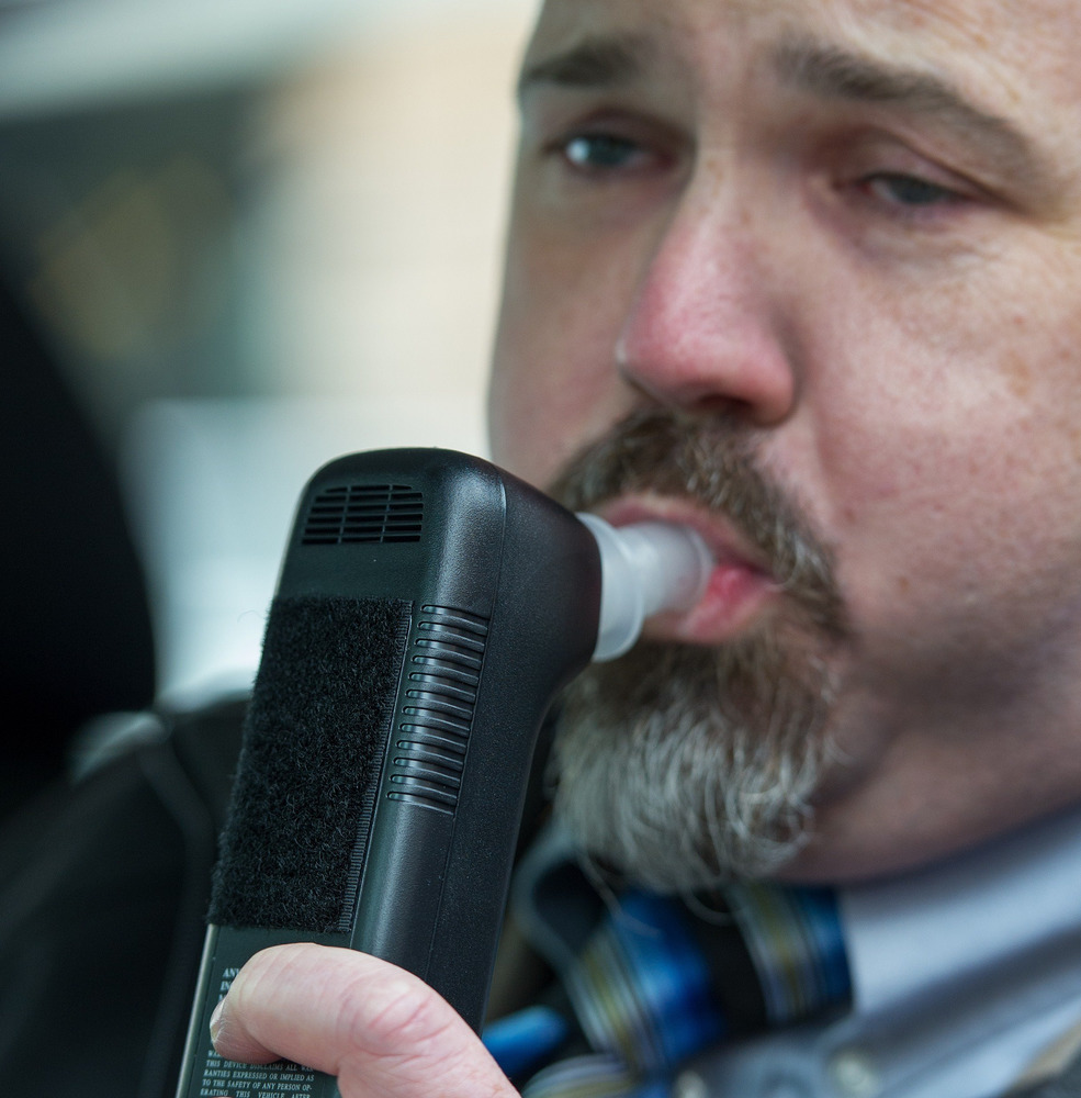 Bill Chastain, state director with LifeSafer, demonstrates a breath alcohol ignition interlock device during a