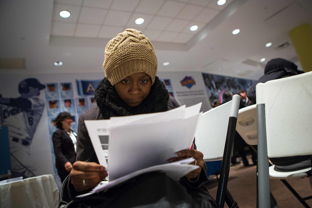 A woman fills out paperwork at a job training and resource fair at Coney Island in New York, Dec. 11, 2013.
