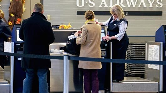 Travelers check in at the US Airways ticket counter at the Pittsburgh International Airport.