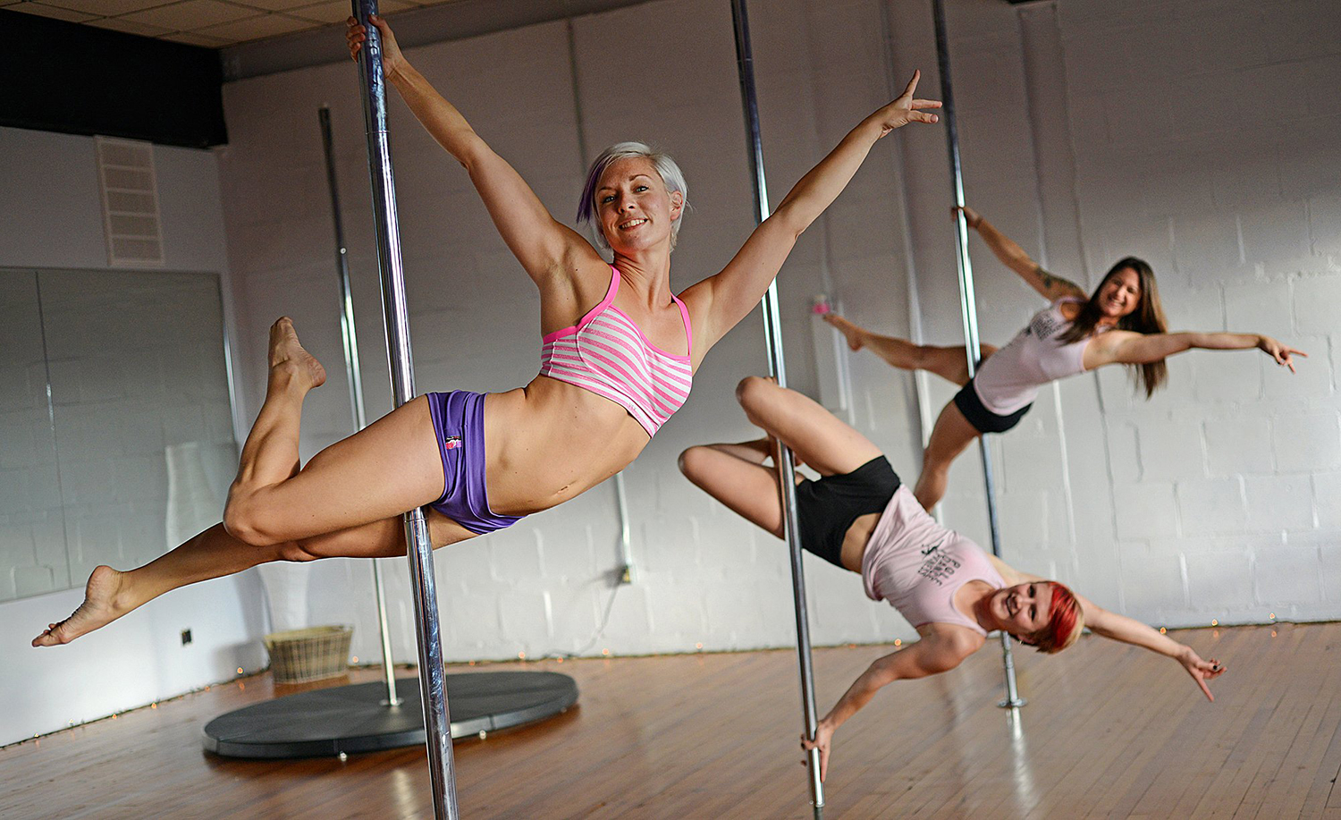 ADVANCE FOR RELEASE SATURDAY, NOV. 9, 2013, AND THEREAFTER - In this October 2013 photo, Pole Dance Fitness studio owner Lucy Howard, front, and stude...