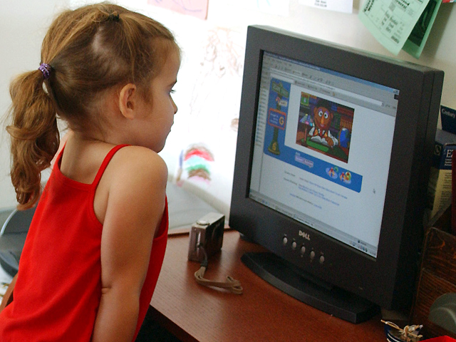 Amanda Cunningham watches as her daughter Madeline Cunningham, 4, uses the computer in her apartment in New York's Upper West Side neighborhood, Thurs...