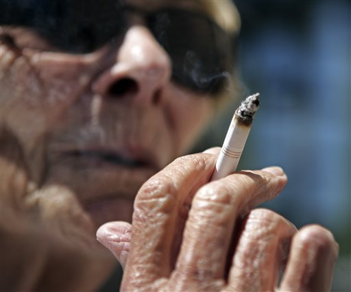 FILE - In this June 11, 2007 file photo, Helen Heinlo smokes outside of a coffee shop in Belmont, Calif.  Some smokers trying to get coverage in 2014 ...