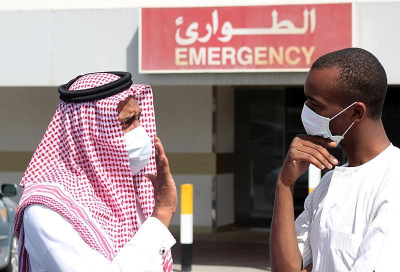 Men wearing surgical masks as a precautionary measure against the novel coronavirus, speak at a hospital in Khobar city in Dammam May 23, 2013. REUTER...