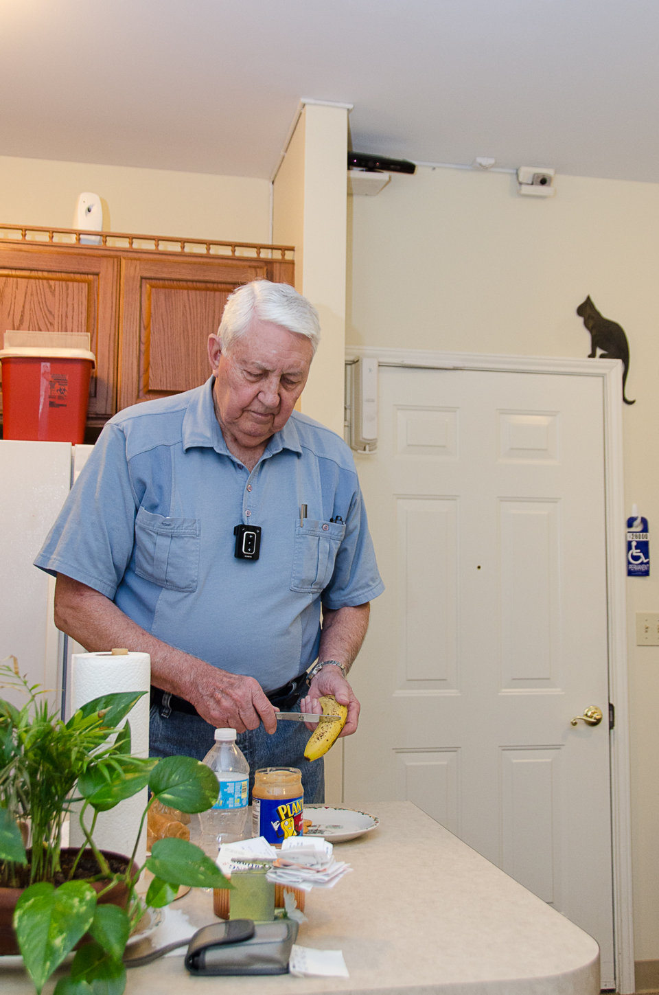In this May 22, 2013 photo provided by the University of Missouri, Bob Harrison prepares a snack in his TigerPlace apartment in Columbia, Mo., as different sensors mounted near the ceiling record activity patterns. The sensor technology is unobtrusive and does not interfere with his everyday tasks. Researchers at the University of Missouri are studying high-tech monitoring systems that promise new safety nets for seniors living on their own.