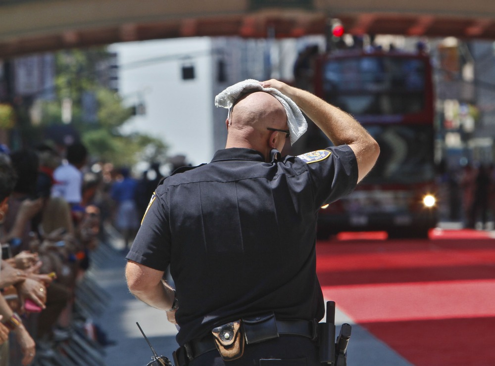 Image: A New York police officer wipes away sweat