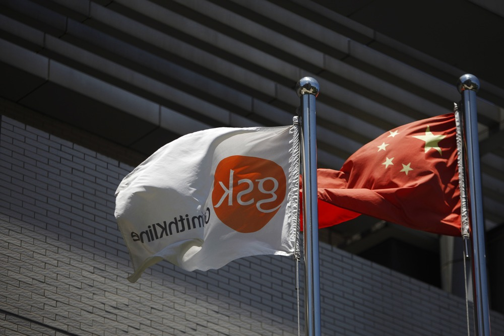 A flag (L) bearing the logo of GlaxoSmithKline (GSK) flutters next to a Chinese national flag outside a GlaxoSmithKline office building in Shanghai Ju...