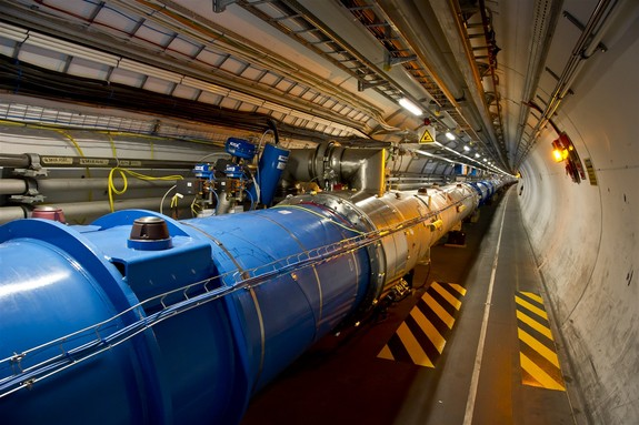 The tunnel of the Large Hadron Collider, where beams of particles pass through the central pipes before colliding with each other.