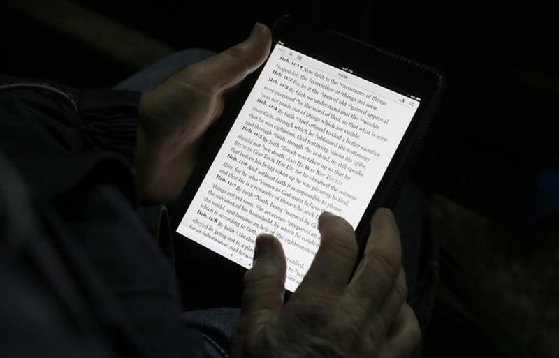A man reads the bible from an iPad mini at the