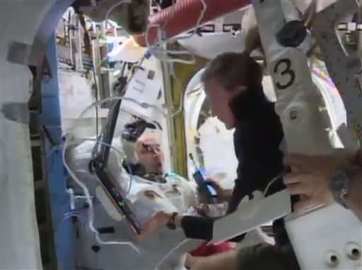 In this image from video made available by NASA, astronaut Karen Nyberg assists astronaut Luca Parmitano remove his space suit after the aborted space...