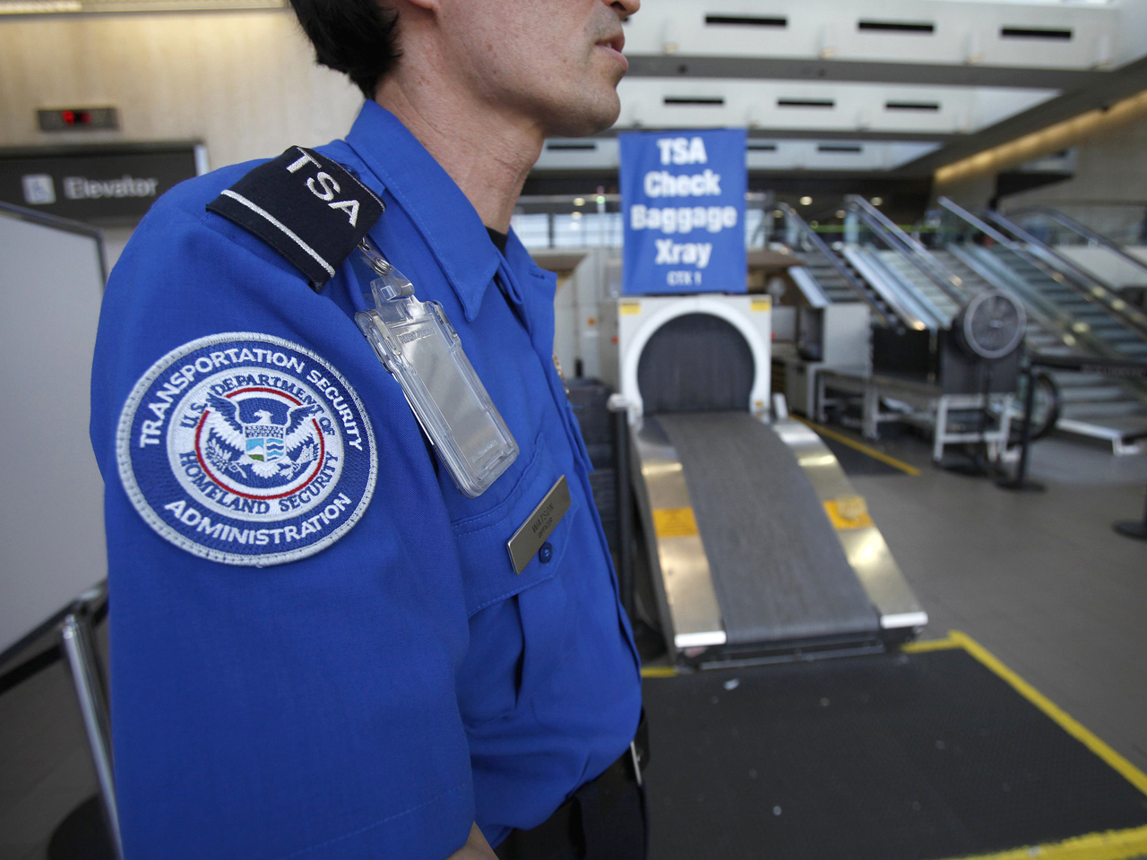 A Transportation Security Administration (TSA) officer waits by an X-ray machine at Los Angeles International Airport in Los Angeles, California March...