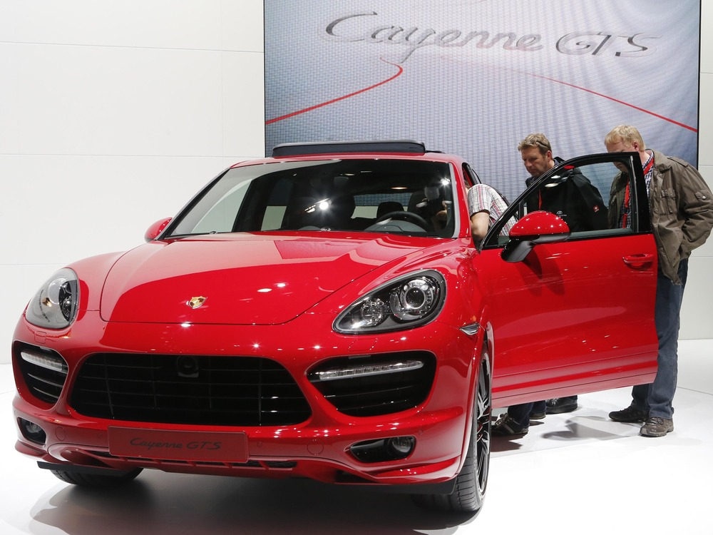 People watch a Porsche Cayenne GTS car during a press preview day at the AMI Auto Show in Leipzig June 1, 2012. The show opens to the public on June 2...