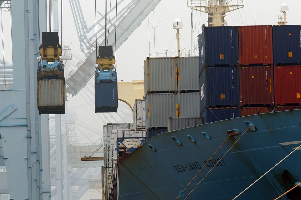 In this Wednesday, Dec.  5, 2012 file photo, containers are unloaded from cargo ships at APM Terninals in the Port of Los Angeles.