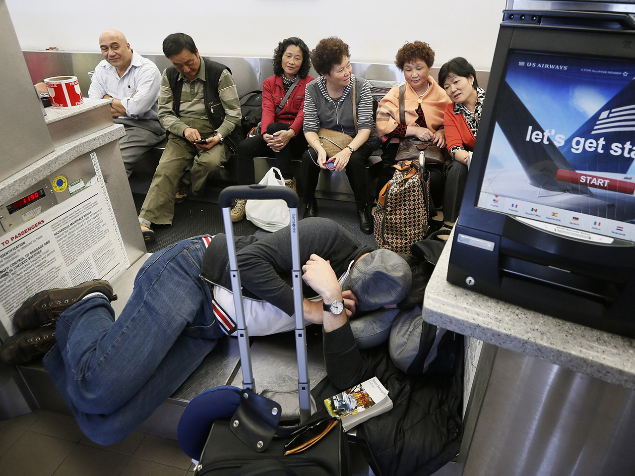 Delayed passengers sit on a baggage conveyer belt after a shooting incident Friday at Los Angeles International Airport.