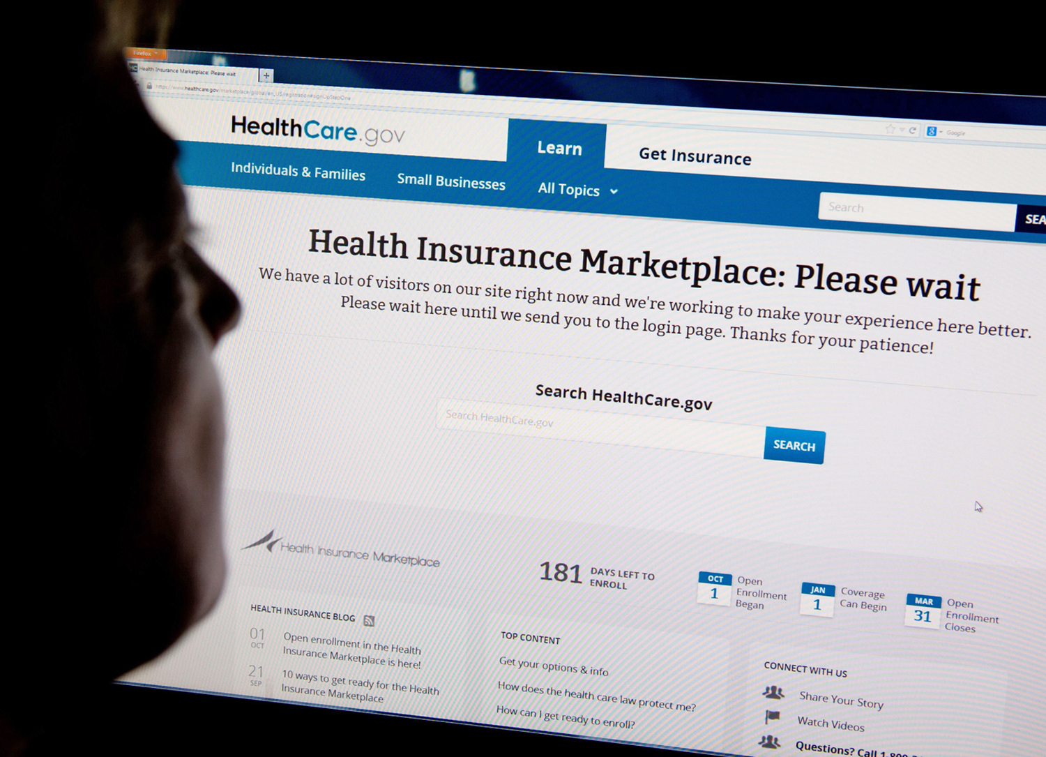 A woman looks at the HealthCare.gov insurance exchange internet site showing a