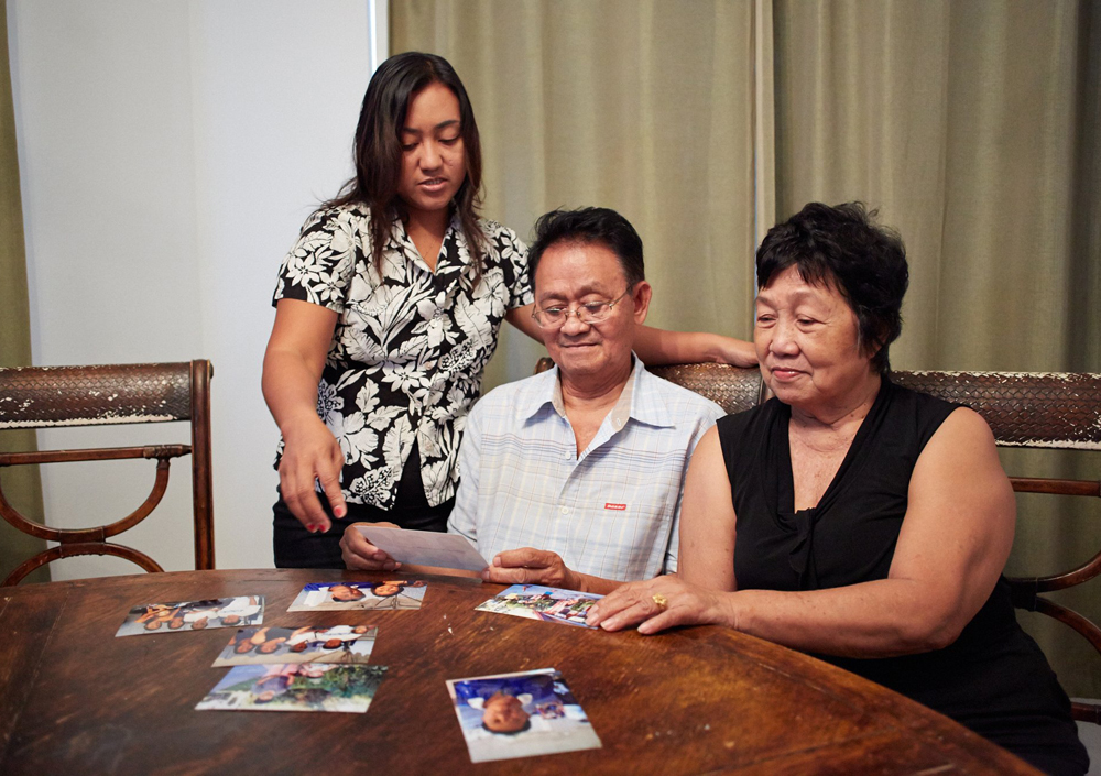 Maribel Barton, left, lost two sisters, three nieces and two nephews when Typhoon Haiyan hit her hometown of Tacloban. She looked over family photos o...