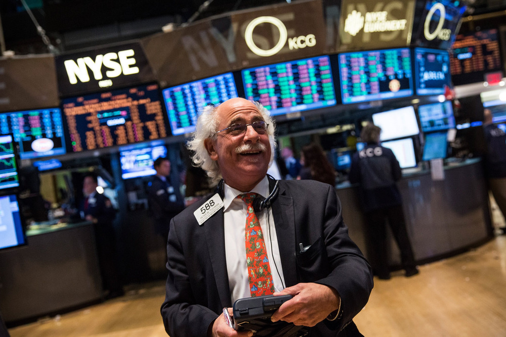 Why is this man smiling? The Dow closed above 16,000 for the first time, buoyed by upbeat economic news.