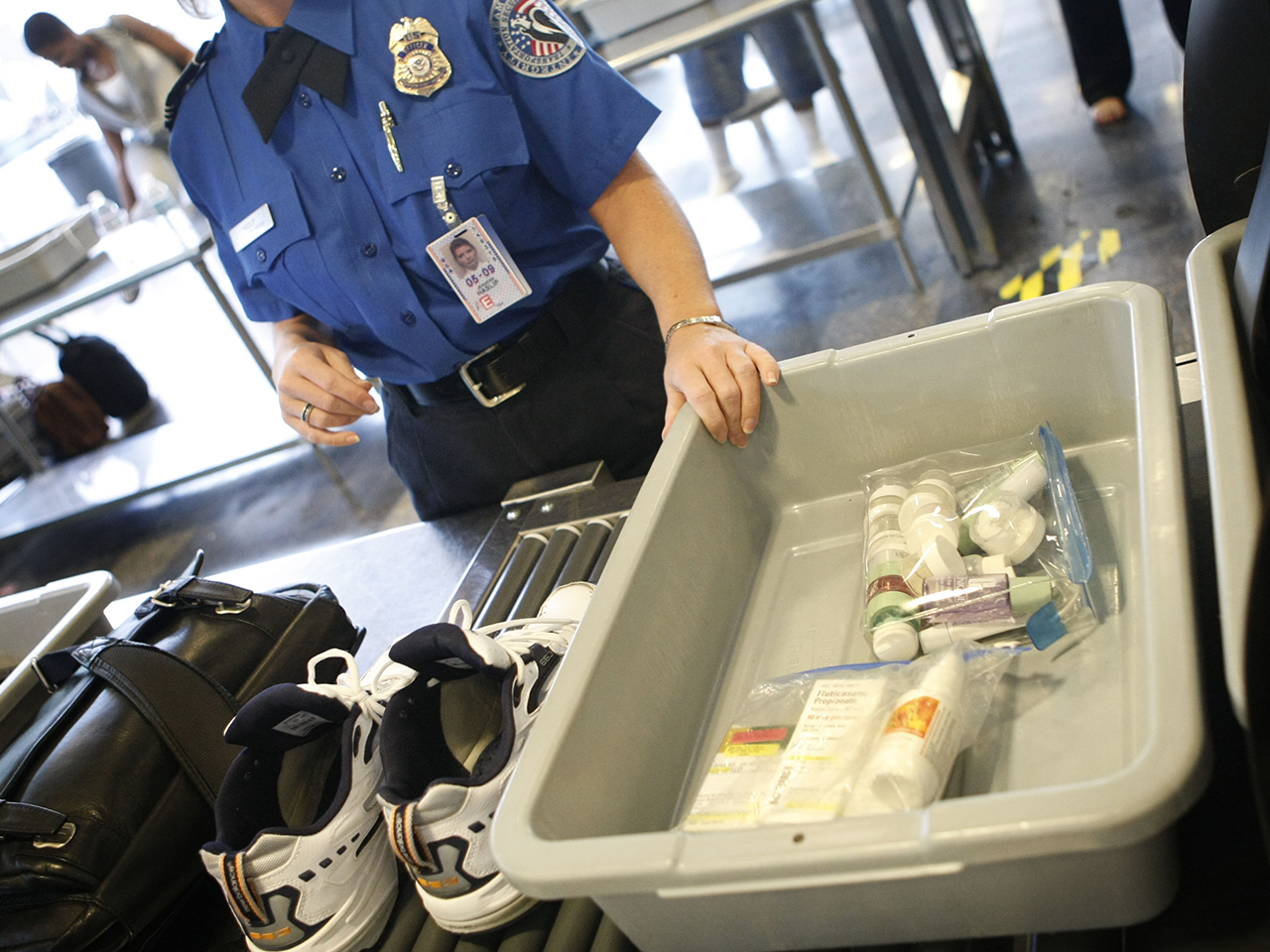 Shoes and small liquid containers are placed in bins to be screened by TSA Supervisor Jennifer Haslip at the x-ray machine at Washington's Ronald Reag...