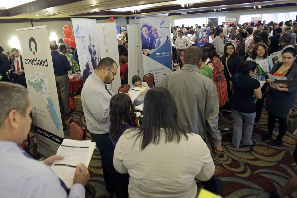 Job seekers check out companies at a job fair in Miami Lakes, Fla. A private survey says hiring remained essentially slow and steady in September.
