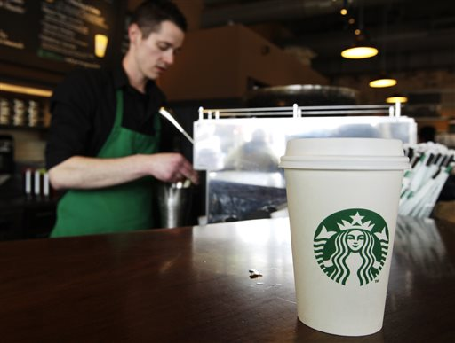 A Starbucks drink waits for a customer to pick it up as barista Josh Barrow prepares another in Seattle in this April 2012 file photo. Starbucks CEO Howard Schultz wants lawmakers to come together to resolve their political gridlock.