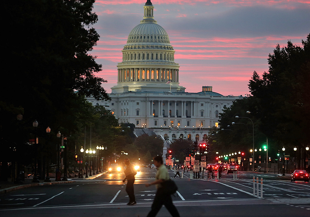 WASHINGTON, DC - OCTOBER 17:  The sun begins to rise behind the U.S. Capitol building on the morning after a bipartisan bill was passed by the House a...