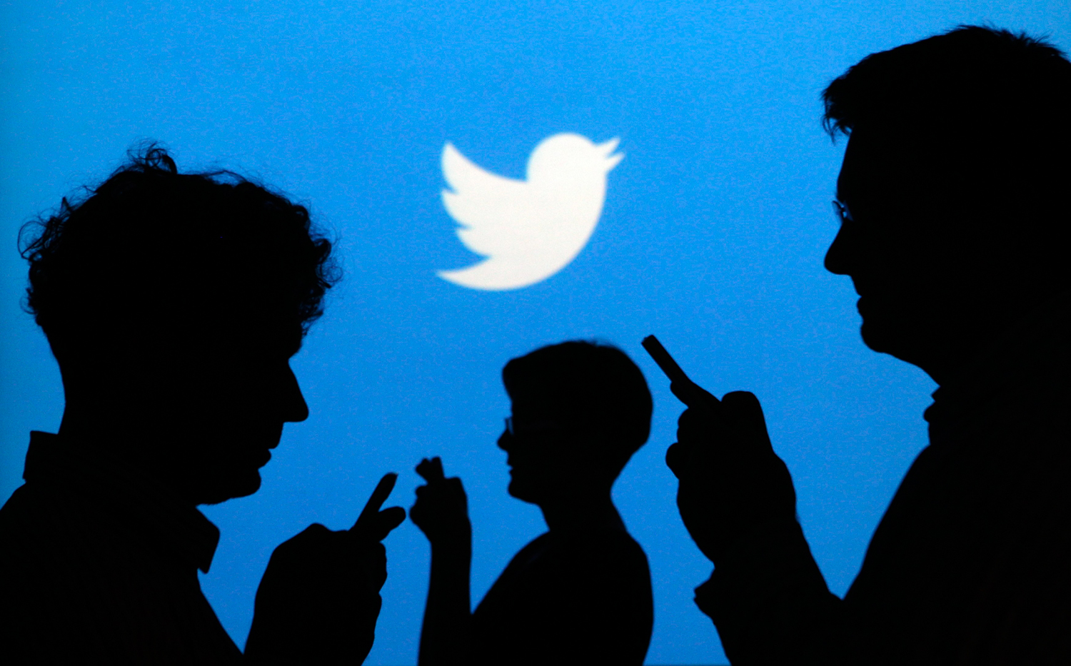 People holding mobile phones are silhouetted against a backdrop on which the Twitter logo is projected, in this file picture illustration taken in War...