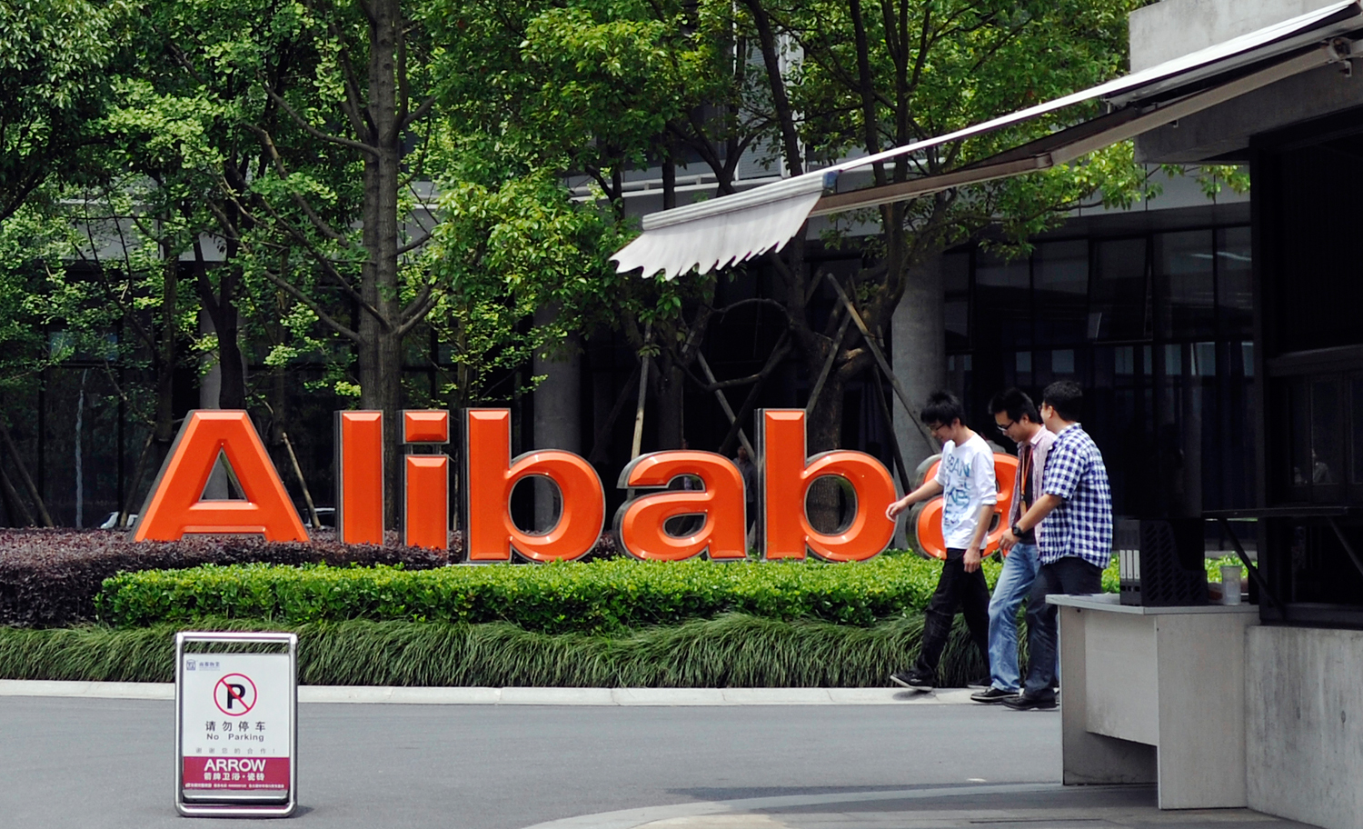 FILE - In this May 21, 2012 file photo, a group of men walk past the corporate logo at the headquarters compound of Alibaba Group in Hangzhou in easte...