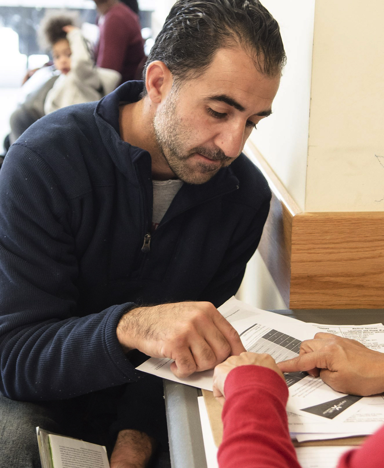 Martha Lopez of Community Clinics, Inc [R] explains to Amine Ashkar(L) of Burtonville, Md benefits that he and his family would receive under the new ...