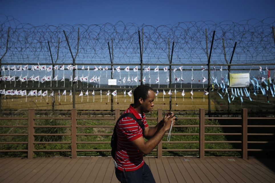 Tourist at DMZ fence in Korea takes picture.